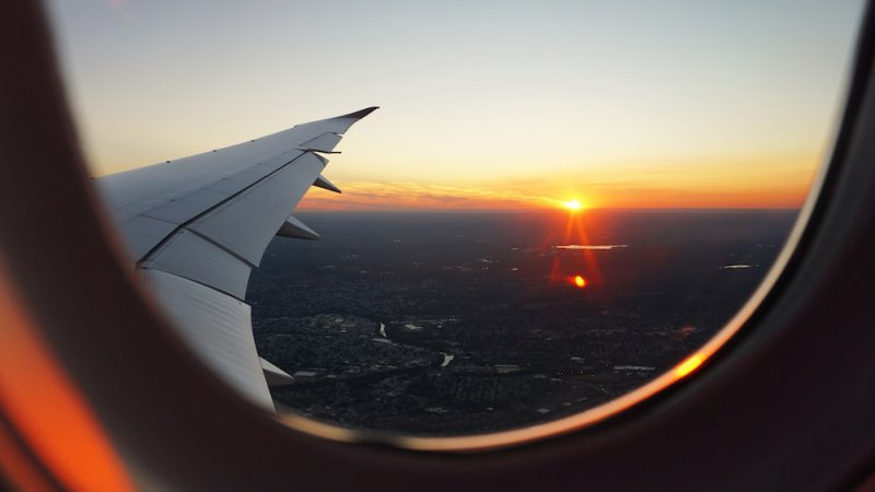looking out of an airplane window to the sunset over the wing