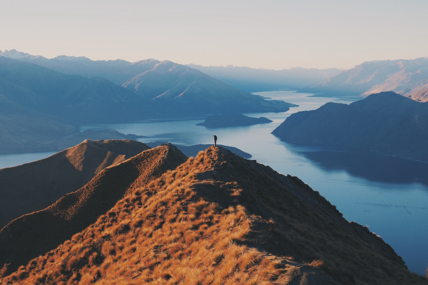 hiker on top of roys peak in wanaka on the south island of new zealand